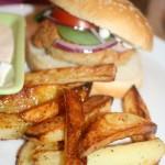 Tonfiskburgare i bröd och kripsiga potatisklyftor, samt kall sås